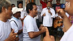Menteri Perhubungan Budi Karya Sumadi bernyanyi saat nongkrong bareng sopir angkot di Tangerang, Banten, Sabtu (26/1). Budi mendengar banyak masukan dari para sopir angkot tentang permasalahan yang mereka alami. (Liputan6.com/Angga Yuniar)