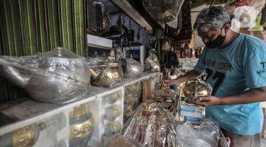 Budi (54) merapikan barang yang dijual di toko oleh-oleh haji di Jalan Raya Pondok Gede, Jakarta, Rabu (21/7/2021). Larangan ibadah haji dan umrah akibat pandemi di Indonesia menyebabkan penjualan oleh-oleh khas Makkah di depan Asrama Haji Pondok Gede merosot tajam. (merdeka.com/Iqbal S. Nugroho)