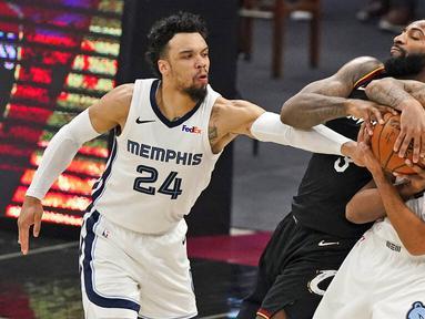 Pebasket Memphis Grizzlies, Dillon Brooks dan Brandon Clarke, berusaha merebut bola dari pebasket Cleveland Cavaliers, Andre Drummond, pada laga NBA, Senin (11/1/2021). Grizzlies menang dengan skor 101-91. (AP/Tony Dejak)