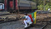 Seorang demonstran membawa bendera nasional Myanmar duduk di rel kereta api yang diblokir dengan kayu, dalam upaya untuk mengganggu layanan kereta selama protes terhadap kudeta militer di Mandalay, Myanmar (17/2/2021). (AP Photo)