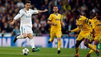 Pemain Real Madrid, Cristiano Ronaldo menendang bola dengan dibayangi pemain Juventus pada leg kedua babak perempat final Liga Champions di Santiago Bernabeu, Rabu (11/4). Real Madrid melaju ke semifinal meski kalah 1-3 dari Juventus. (AP/Paul White)