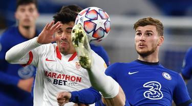 Striker Chelsea, Timo Werner, berebut bola dengan Gelandang Sevilla, Marcos Acuna, pada laga Grup E Liga Champions 2020/2021 di Stamford Bridge, Rabu (21/10/2020) dini hari WIB. Chelsea bermain imbang 0-0 atas Sevilla. (AFP/Glyn Kirk/pool)