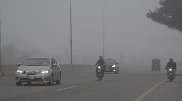 Kendaraan melaju di sebuah jalan di tengah kabut tebal di Kota Lahore, Pakistan timur, pada 13 Desember 2020. Kabut tebal menyelimuti sejumlah kota di Pakistan, sehingga meminimalkan jarak pandang dan mengganggu lalu lintas jalan. (Xinhua/Sajjad)