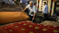 Pedagang memamerkan karpet tenun dagangannya kepada pengunjung pameran di Teheran, Iran, Kamis (29/8/2019). AS menghentikan impor karpet Iran setelah Presiden Donald Trump menjatuhkan sanksi terkait program nuklir negara tersebut. (AP Photo/Vahid Salemi)