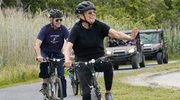 Presiden Joe Biden bersama ibu negara, Jill Biden bersepeda di Pantai Rehoboth, Delaware, Kamis (3/6/2021). Mereka bersepeda sekaligus untuk merayakan ulang tahun ke-70 ibu negara Amerika Serikat. (AP Photo/Susan Walsh)