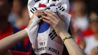 Seorang warga menutupi wajahnya dengan bendera Korea Selatan usai timnasnya dikalahkan Belgia 0-1, Seoul, Jumat (27/6/14). (REUTERS/Kim Hong-Ji)