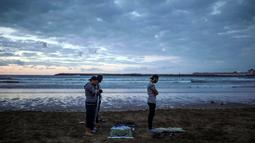 Sejumlah pria salat Maghrib berjamaah usai buka puasa bersama di pantai Rabat, Maroko (9/6). Selama Ramadan, banyak warga Maroko berkunjung ke pantai menikmati angin Atlantik dan menikmati pemandangan laut. (AP Photo/Mosa'ab Elshamy)