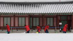 "Sejumlah wanita mengenakan pakaian tradisional Korea ""Hanbok"" membersihkan salju di Istana Gyeongbok di Seoul, Korea Selatan (15/2). Istana Gyeongbok aslinya didirikan tahun 1394 oleh Jeong do jeon, seorang arsitek.  (AP Photo/Ahn Young-joon)"