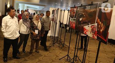 Mantan Wakil Presiden, yang juga Ketua Umum Palang Merah Indonesia (PMI) Jusuf Kalla (kiri) menyaksikan jajaran foto kegiatan anggota PMI saat Musyawarah Nasional XXI PMI, di Jakarta, Selasa (17/12/2019). Jusuf Kalla kembali memimpin PMI untuk periode 2019-2024. (Liputan6.com/Herman Zakharia)