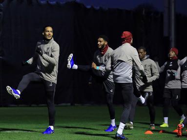 Bek Liverpool Belanda Virgil van Dijk (kiri) bersama rekan-rekannya melakukan pemanasan saat sesi latihan di Melwood, Inggris (26/11/2019). Liverpool akan bertanding melawan wakil Italia, Napoli pada Grup E Liga Champions di Anfield. (AFP/Lindsey Parnaby)