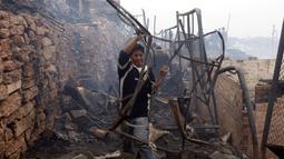 Warga mengambil besi dari puing-puing bangunan menyusul kebakaran yang melanda permukiman Cantagallo di Lima, Peru, Jumat (4/11). Pejabat setempat mengatakan, ada 46 orang yang sempat dirawat akibat terlalu banyak menghirup asap. (REUTERS/Guadalupe Pardo)