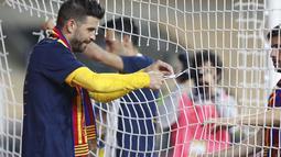 Bek Barcelona, Gerard Pique memotong sebagian jala gawang saat mereka merayakan kemenangan atas Athletic Bilbao pada final Copa del Rey Spanyol 2021 di stadion La Cartuja di Seville, Spanyol, Minggu (18/4/2021). Barcelona menang atas Athletic Bilbao 4-0. (AP Photo / Angel Fernandez)