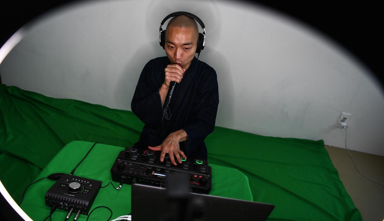 Foto yang diambil pada 26 Juni 2020 menunjukkan, Yogetsu Akasaka, seorang biksu Buddha yang juga seniman beatbox, menampilkan pertunjukan beatboxing secara live streaming di rumahnya di Tokyo. (CHARLY TRIBALLEAU/AFP)