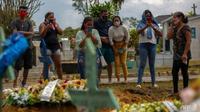 Kerabat korban COVID-19 menghadiri pemakaman di Brasil, di mana jumlah kematian setiap hari melonjak. (AFP / MICHAEL DANTAS)