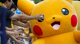 Warga bersuka cita menunggu parade Pikachu dalam serial animasi Pokemon melakukan parade di Yokohama , Jepang , 7 Agustus 2016. (REUTERS / Kim Kyung - Hoon)