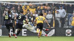 Dele Alli (kiri) menjadi keran gol Tottenham lewat tendangan pinalti setelah dirinya dijatuhkan di kotak dua belas pas. Ia sukses melesatkan bola ke sudut kiri dari arah kiper Wolves, Jose Sa. Papan skor berubah menjadi 1-0 dengan keunggulan The Lilywhites. (Foto: AP/Rui Vieira)