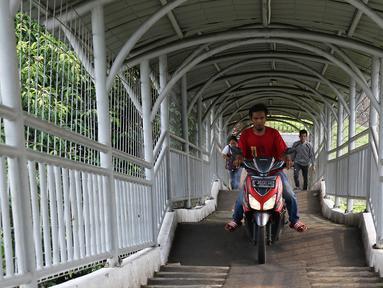 Pengendara sepeda motor melewati Jembatan Penyeberangan Orang (JPO) di kawasan Pasar Minggu, Jakarta, Selasa (17/10). JPO yang diperuntukkan bagi pejalan kaki itu sering dimanfaatkan pengendara motor sebagai jalan pintas. (Liputan6.com/Immanuel Antonius)