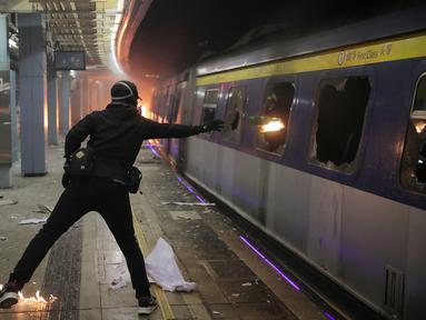 Seorang pelajar melempar bom molotov ke dalam kereta yang terparkir di Stasiun MTR Chinese University, Hong Kong, Rabu (13/11/2019). Gerakan antipemerintah Hong Kong yang telah berlangsung selama lima bulan bertindak semakin keras. (AP Photo/Kin Cheung)