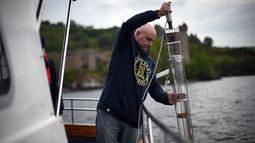Ahli genetika Universitas Otago Profesor Neil Gemmell mengambil sampel air dari perairan Loch Ness, Drumnadrochit, Skotlandia, 11 Juni 2018. Tim dari Selandia Baru menguji kebenaran dari keberadaan moster raksasa Loch Ness. (Andy Buchanan/AFP)