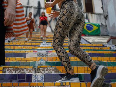 Orang-orang berlalu-lalang di anak tangga yang terkenal dengan nama Selaron Steps atau Escadaria Selarón di Rio de Janeiro, Brasil pada 9 Desember 2019. Escadaria Selaron merupakan 250 anak tangga sepanjang 125 meter dengan dua ribuan ubin berwarna-warni. (Photo by David GANNON / AFP)