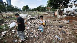 Anak-anak bermain di makam yang tertutup sampah di TPU Menteng Pulo 2, Jakarta, Senin (9/12/2019). Minimnya kesadaran warga setempat ditambah tidak adanya fasilitas TPA dan perawatan pengelola TPU menyebabkan kondisi kompleks makam memprihatinkan akibat dipenuhi sampah.(merdeka.com/Iqbal S. Nugroho)