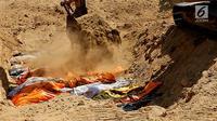 Puluhan jenazah dikubur massal menggunakan eskavator di TPU Peboya Indah, Palu, Sulawesi Tengah, Rabu (3/10). Jenazah yang merupakan korban gempa tsunami dikubur tiga lapis. (Liputan6.com/Fery Pradolo)