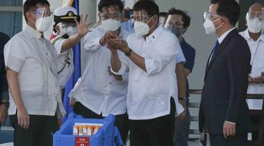 Presiden Rodrigo Duterte memegang vaksin COVID-19 Sinovac gelombang pertama yang tiba di negaranya, 28 Februari 2021 (AP Photo)