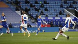 Striker Crystal Palace, Wilfried Zaha (kanan) melepaskan tendangan yang berbuah gol ke gawang Leicester City dalam laga lanjutan Liga Inggris 2020/2021 pekan ke-33 di King Power Stadium, Leicester, Senin (26/4/2021). Leicester menang 2-1 atas Crystal Palace. (AP/Andrew Boyers/Pool)