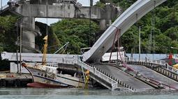 Sebuah kapal nelayan tertimpa jembatan beton yang ambruk di pelabuhan ikan Nanfangao di kota Suao (1/10/2019). Kejadian tersebut membuat setidaknya 14 orang terluka. (AFP Photo/Sam Yeh)