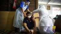 Petugas medis menyuntikan vaksin COVID-19 Pfizer kepada pria lansia di rumahnya di pedesaan Sabab Bernam, Selangor, Malaysia, Selasa (13/7/2021). Tim medis pergi dari rumah ke rumah di desa terpencil untuk menjangkau warga lansia dalam upaya meningkatkan program vaksinasi. (AP Photo/Vincent Thian)