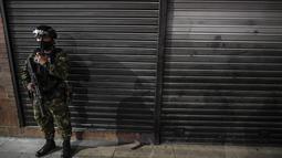 """Seorang tentara polisi militer Kolombia berpatroli di jalan-jalan di Bogota (15/9/2021). Ratusan tentara telah berpatroli di jalan-jalan Bogotá sejak Rabu dalam upaya """"sementara"""" oleh pihak berwenang untuk mengendalikan gelombang perampokan dengan kekerasan. (AFP/Juan Barreto)"""
