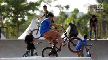 Beberapa anak mencoba memainkan sepeda di area RTH Kalijodo, Rabu (20/6). Banyaknya pilihan permainan buat anak-anak menjadikan RTH Kalijodo memiliki daya tersendiri untuk menghabiskan waktu libur bersama keluarga. (Lipiutan6.com/Helmi Fithriansyah)