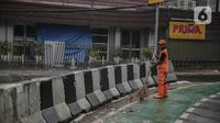 Petugas PPSU membersihkan sampah dekat beton pembatas di Jalan Senopati, Jakarta, Minggu (29/12/2019). Pascakejadian mobil tabrak Apotek Senopati, Suku Dinas Bina Marga memasangan beton pembatas untuk meminimalisir kejadian serupa terulang kembali. (Liputan6.com/Faizal Fanani)