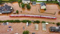Sebuah kereta api regional terendam banjir setelah dibanjiri oleh tingginya air sungai Kyll di Kordel, Jerman, Kamis (15/7/2021). Sekitar 6.000 orang di munisipalitas Heimerzheim harus dievakuasi, sementara rumah dan harta benda mereka diterjang banjir. (Sebastian Schmitt/dpa via AP)