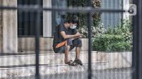 Seorang pasien positif Covid-19 melihat ponselnya saat menjalani isolasi mandiri di sebuah hotel kawasan Salemba, Jakarta, Senin (22/2/2021). Hotel masih menjadi pilihan warga di Jakarta sebagai tempat isolasi mandiri ketika terpapar virus Covid-19. (merdeka.com/Iqbal S. Nugroho)