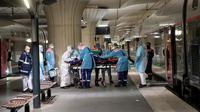 Petugas medis membawa pasien virus corona COVID-19 di Stasiun Gare d'Austerlitz di Paris, Prancis, Rabu (1/4/2020). Pasien COVID-19 dievakuasi menggunakan kereta kecepatan tinggi dari rumah sakit di Paris ke rumah sakit di Brittany dimana kasus tersebut masih terbatas. (Thomas SAMSON/AFP/POOL)