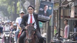 Motivator Tung Desem Waringin mempromosikan buku terbarunya berjudul 'Life Revolution' dengan berkuda di Jakarta, Kamis (7/6). Life Revolution merupakan buku ketiga yang dibuat Tung Desem Waringin. (Liputan6.com/Faizal Fanani)