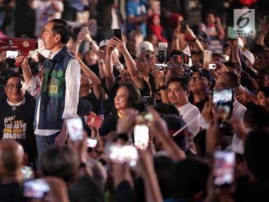 Calon presiden nomor urut 01, Joko Widodo (Jokowi) menggunakan megaphone berwarna merah menyapa para alumni saat menghadiri Deklarasi Alumni Trisakti di Hall Basket, Senayan, Jakarta, Sabtu (9/2). (Liputan6.com/Faizal Fanani)