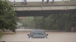 Sebuah mobil terjebak banjir di Sao Paulo, Brasil, Senin, (10/2/2020). Hujan deras yang membanjiri kota, menyebabkan pinggir sungai utama meluap. (AP Photo/Andre Penner)