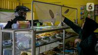 Penjual melayani pembeli di warteg kawasan Jakarta, Rabu (27/1/2021). Komunitas Warteg Nusantara (Kowantara) menyatakan, sekitar 50 persen atau 20.000 unit warteg di Jabodetabek akan gulung tikar tahun ini disebabkan tidak mampu membayar atau memperpanjang sewa tempat. (Liputan6.com/Faizal Fanani)