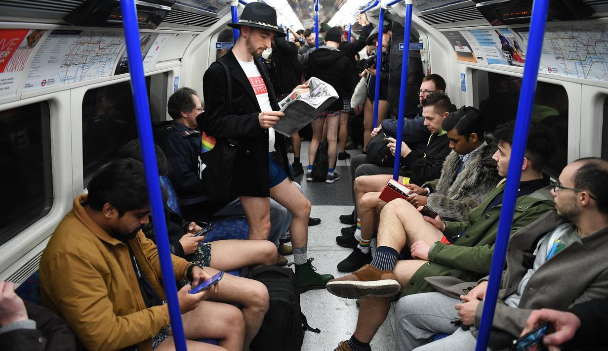 Orang-orang mengambil bagian dalam 'No Trousers On The Tube Day' atau No Pants Subway Ride di London Underground,  pusat Kota London, Minggu (12/1/2020). Untuk tahun ini, acara naik kereta tanpa celana itu dilangsungkan serentak di sejumlah kota dunia pada 12 Januari. (DANIEL LEAL-OLIVAS/AFP)