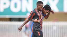 Pemain belakang tim sepakbola putra NTT Frengky Missa membantu  pemain  tim sepakbola putra Papua Hermando Walilo yang mengalami cedera pada laga Grup A PON XX Papua 2021. (Foto: PB PON XX Papua/Chaarly Lopulua)