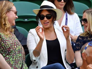 Meghan Markle (tengah) menyaksikan sahabatnya yang juga petenis AS Serena Williams melawan Kaja Juvan dari Slovakia pada babak kedua Wimbledon di All England Lawn Tennis Club, London, Kamis (4/7/2019). Meghan Markle tampil dalam balutan tank top dan jeans dengan blazer sebagai luaran (GLYN KIRK/AFP)