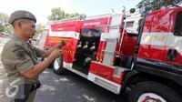 Petugas pemadam kebakaran mengerahkan Mobil Damkar di tempat kejadian kebakaran di kawasan Hj. Nawi, Jakarta, Senin (20/7/2015). Pemadam kebakaran mengerahkan 13 unit mobil Damkar di tempat kejadian kebakaran. (Liputan6.com/Helmi Afandi)