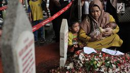 Seorang ibu sambil menggendong bayinya berziarah ke makam Presiden ketiga RI BJ Habibie di TMP Kalibata, Jakarta, Kamis (12/9/2019). Hingga sore hari, warga terus berdatangan ke TMP kalibata untuk dapat berkesempatan mendoakan almarhum BJ Habibie. (merdeka.com/Iqbal Nugroho)