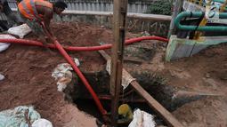 Pekerja memasukkan kabel jaringan utilitas ke dalam tanah di kawasan Kemayoran, Jakarta, Minggu (14/1). PT PLN Disjaya melakukan ini untuk mendukung Pemprov DKI Jakarta mewujudkan smart city. (Liputan6.com/Immanuel Antonius)