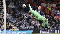 Kiper Republik Ceko, Tomas Vaclik berusaha menepis bola dari sundulan pemain Skotlandia, Lyndon Dykes pada pertandingan grup D Euro 2020 di stadion Hampden Park, Glasgow, Senin (14/6/2021). Dengan kemenangan ini, Ceko menggeser Inggris dari puncak klasemen sementara. (Stu Forster, Pool via AP)