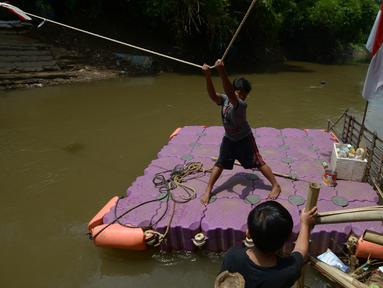 Anak-anak menggunakan perahu eretan di sungai Ciliwung, Jakarta, Selasa (3/11/2020). Perahu eretan di sungai Ciliwung masih bertahan sebagai penghubung Jakarta Timur dan Jakarta Selatan Selatan. (merdeka.com/Imam Buhori)