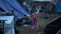 Seorang anak perempuan menyapu tempat penampungan pengungsi korban gempa bumi di Lombok Utara,  NTB, Rabu (8/8). BPBD Lombok Utara mencatat data sementara jumlah korban jiwa akibat gempa Lombok mencapai 347 orang. (AP/Tatan Syuflana)