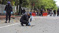 Tim penjinak bom menggeledah area sekitar lokasi serangan bom bunuh diri di Gereja Katedral Makassar, Sulawesi Selatan, Senin (29/3/2021). Kepolisian masih melakukan olah TKP serta mengumpulkan serpihan sisa ledakan pada hari kedua pascaledakan bom bunuh diri di depan gereja itu. (AP/Yusuf Wahil)